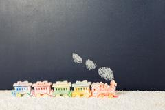 Covered locomotive train toy with smoke in snow on chalkboard background, win Kuvituskuvat