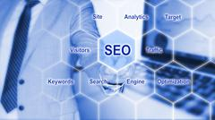 IT expert touches grid with seo keywords Stock Photos