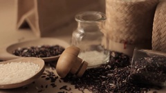 Rice and rice-berry uncooked brown rice in wooden spoon Stock Footage