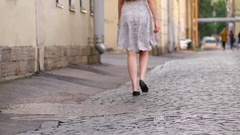Elegant woman come away at sett pavement, low half backside view Stock Footage