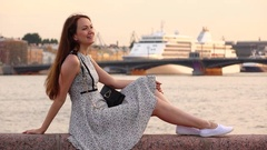 Cheerful woman sit on parapet and laugh, against city river and white ship Stock Footage