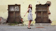 Carefree woman twirl against old shabby building, look around, slowmo Stock Footage