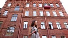 Woman stand outdoors, wait against brick building, drink coffee, low angle shot Stock Footage