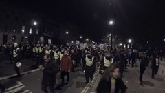 Million Mask March protestors wearing Guy Fawkes masks escorted by police Stock Footage