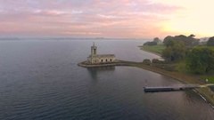Approaching beautiful lakeside church in the sunrise. Aerial view Stock Footage