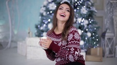 Girl in bright sweater in front of fir-tree Stock Footage