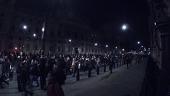 Police escorting Anonymous Million Mask March protestors Guy Fawkes in London Stock Footage