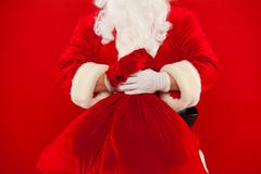 Santa Claus hand holding red sack full of presents over Stock Photos
