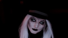 Girl in the image of a witch hat. Black background Stock Footage
