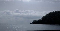 Pebble Coast Line With Glistening and Shimmering Sea Surface With Island on Stock Footage