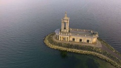 Beautiful church in the lake. Pan around shot. Aerial view Stock Footage