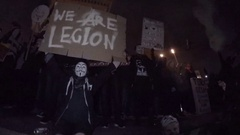 Million Mask March protestors wearing Anonymous mask holding We Are Legion sign Stock Footage