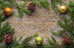 Holiday decoration snow, bells, green branch and pine cones on wooden frozen tab Stock Photos