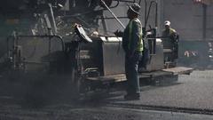 Asphalt paver machine and worker. Stock Footage