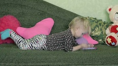 Dolly Little Girl Lying on the Sofa with Smartphone Stock Footage