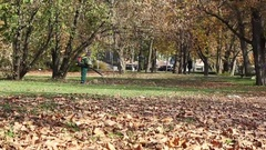 Autumn cleaning park ,worker with leaf blower outdoor ,fall season  Arkistovideo