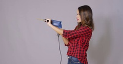 Capable attractive young woman holding a drill Stock Footage