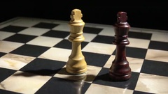 Two chess kings on chessboard that are close to falling. Stock Footage