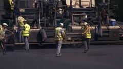 Men with shovels throw asphalt. Stock Footage