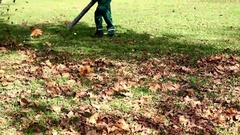 Autumn cleaning park ,worker with leaf blower outdoor ,fall season  Stock Footage