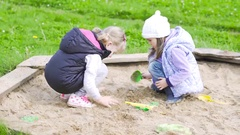 Two girls play in the sandbox Stock Footage