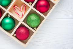 Preparation for Christmas: festive balls and candy cane in wooden box on whit Stock Photos