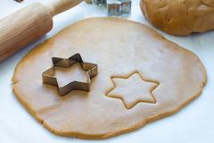 Making gingerbread cookies. Dough, metal cutter and rolling pen on wooden tab Stock Photos