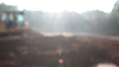 Soft Focus Title Card Screen of Mini Dozer with Light Flare from Sunrise Stock Footage