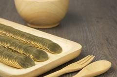 Close up stack of gold coins in wooden tray Stock Photos