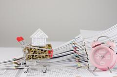 House on shopping cart with gold coins and alarm clock Stock Photos