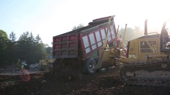 Dump Truck Empties Load and Mini Dozer Moves Load Stock Footage