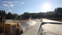 Mini Steam Roller Flattens New Road Paving across Bridge on Sunny Day Stock Footage