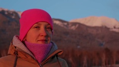 Portrait of a smiling young woman at the foot of the mountains at sunset Stock Footage