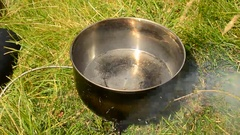 Water boiling in a saucepan on fire outdoors Stock Footage