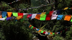 Bhutan prayer flags over a waterfall and mountains Stock Footage