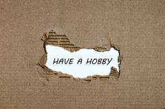 The word have a hobby appearing behind torn paper Stock Photos