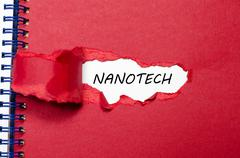 The word nanotech appearing behind torn paper Stock Photos