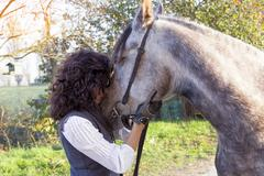 Horsewoman kisses his horse to the country roads in autumn Stock Photos