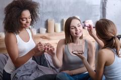 Pleasant girls helping her friend getting ready at home Stock Photos