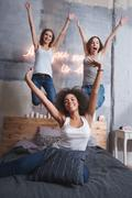 Laughing friends jumping on the bed and having fun Kuvituskuvat