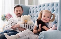 Optimistic joyful girl hugging her kitten Stock Photos