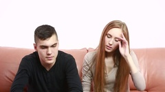 Beautiful young couple conflict sitting on a couch argue unhappy Stock Footage