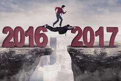 Male entrepreneur leaping on gap aim 2017 Stock Photos