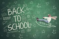 Child with rocket and doodles on the chalkboard Stock Photos