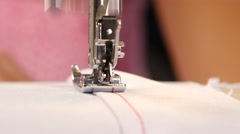 Red stitching on white cloth. Close up Stock Footage