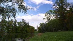 Silent lake shore at old parkland, Tower in medieval castle style seen afar Stock Footage
