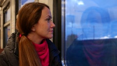 Woman look out train window, optimistic mood, ride at evening through suburbs Stock Footage