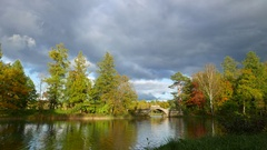 Vivid green colours at early autumn colours, landscaped garden lake stone bridge Stock Footage