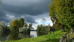 Clouds piling up, lush green trees and grass on shore of small lake Stock Footage