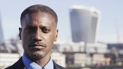 4K Portrait of a serious business man with blurred city behind him, in slow mo Stock Footage